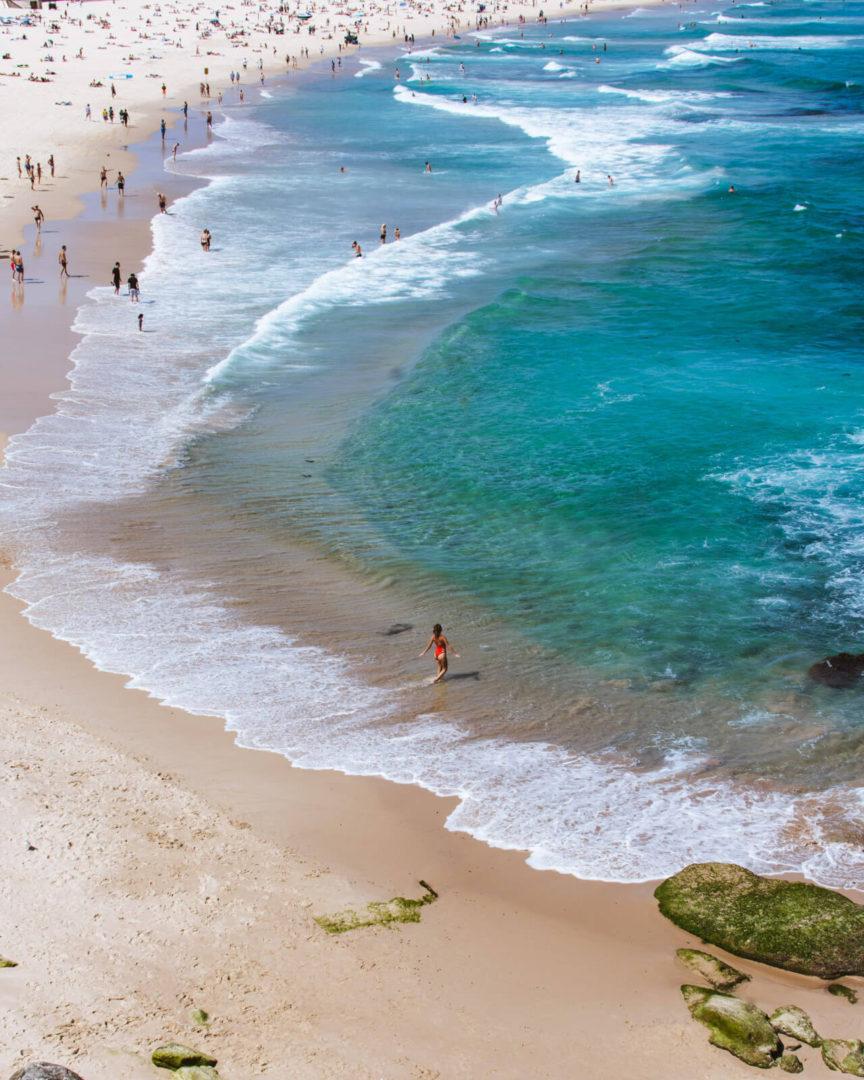 drone shot of girl in red bikini walking into the ocean on bondi beach sydney