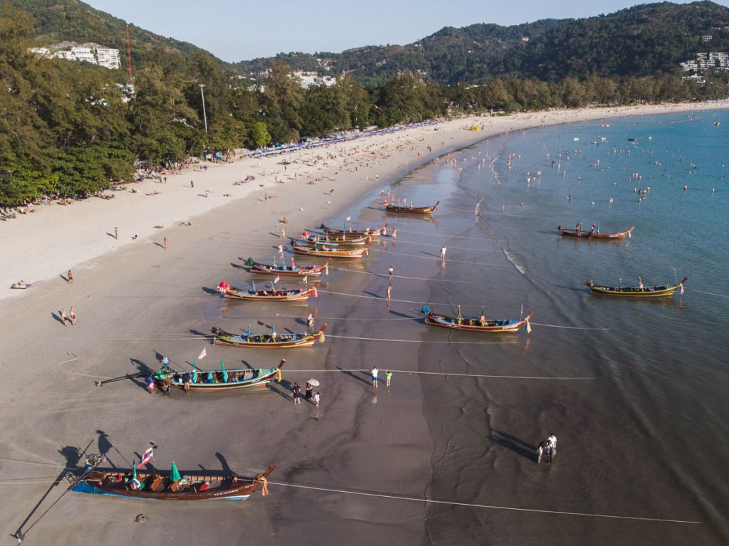 Drone shot of Long-tail boats ashore on the beach