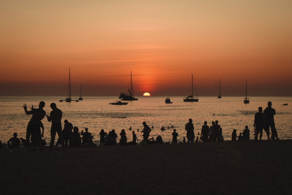 Black silhouettes with sunset on nai harn beach