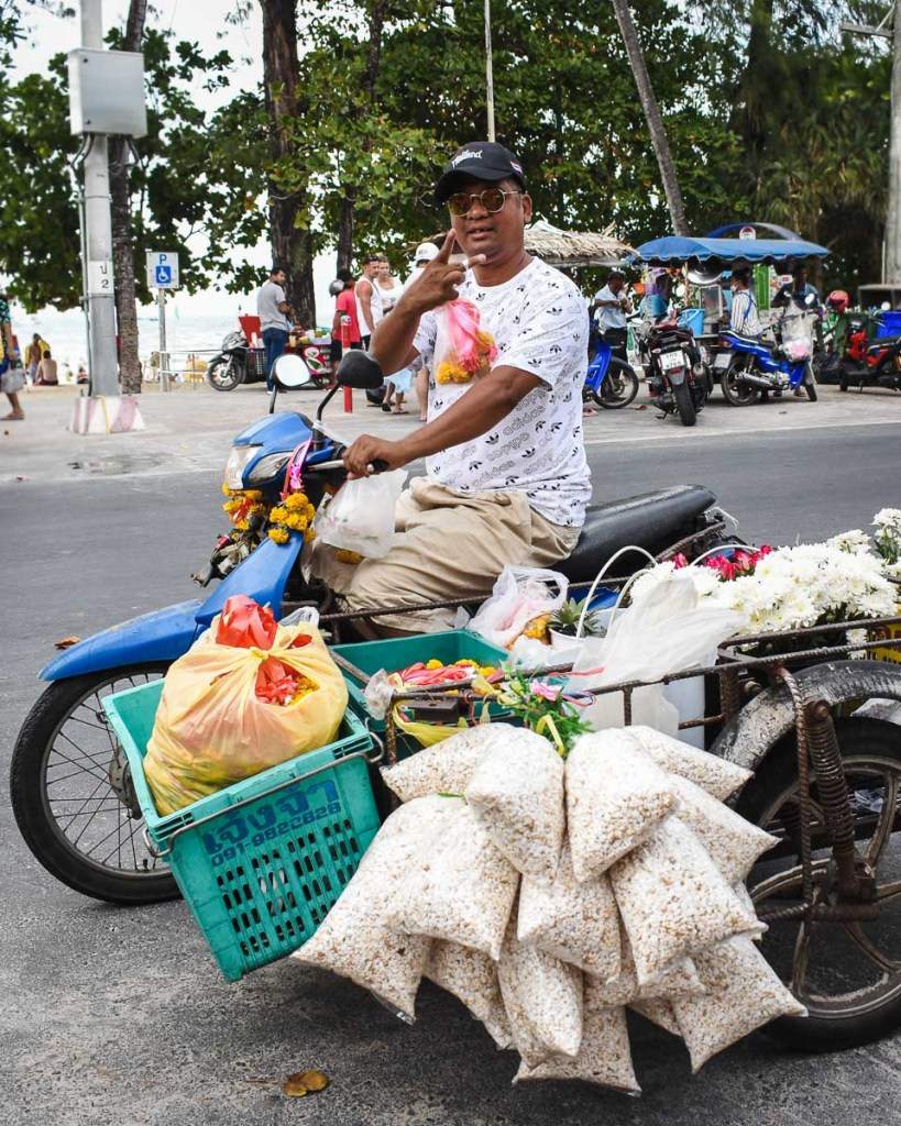 Local taiwanese man on scooter with side cart full of flowers