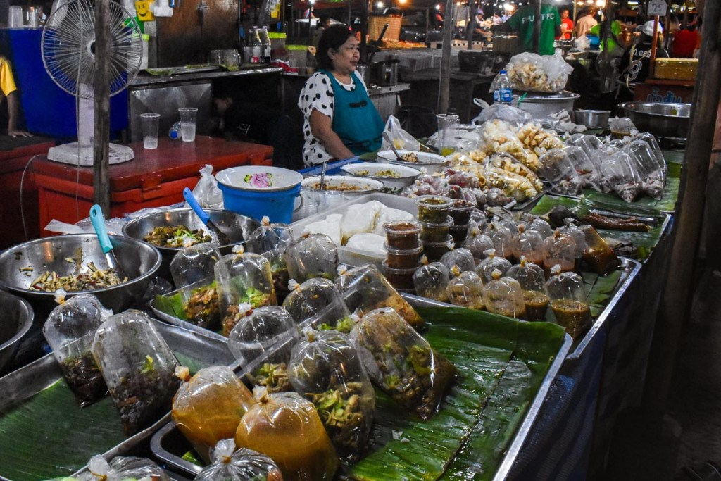 Woman selling local Thai food at a market in Phuket
