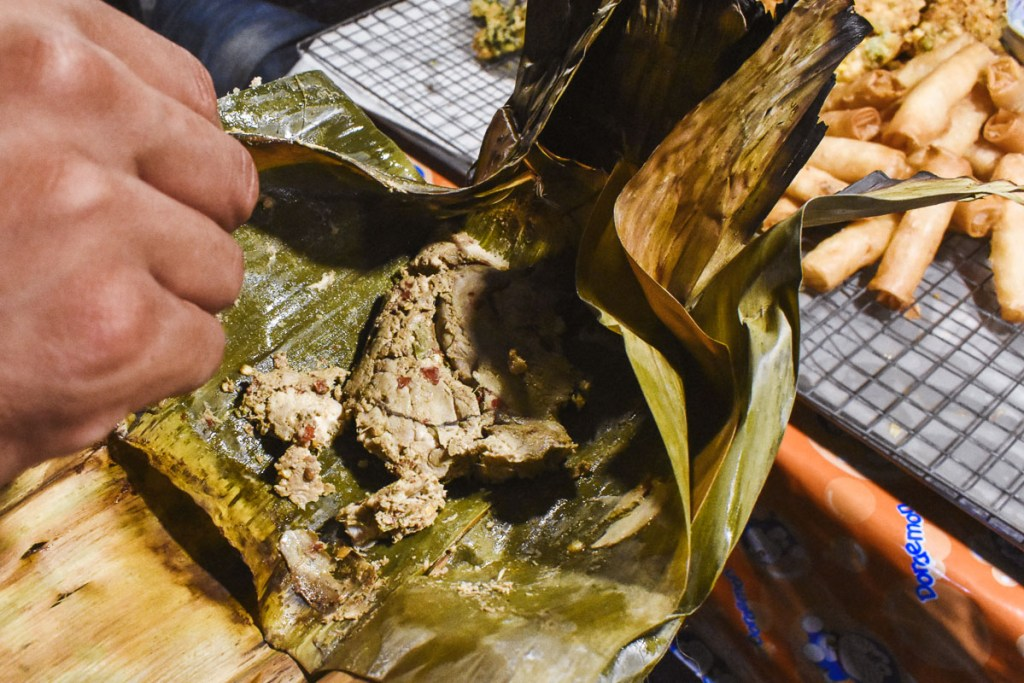 Spicy meat in banana leaf at local food market