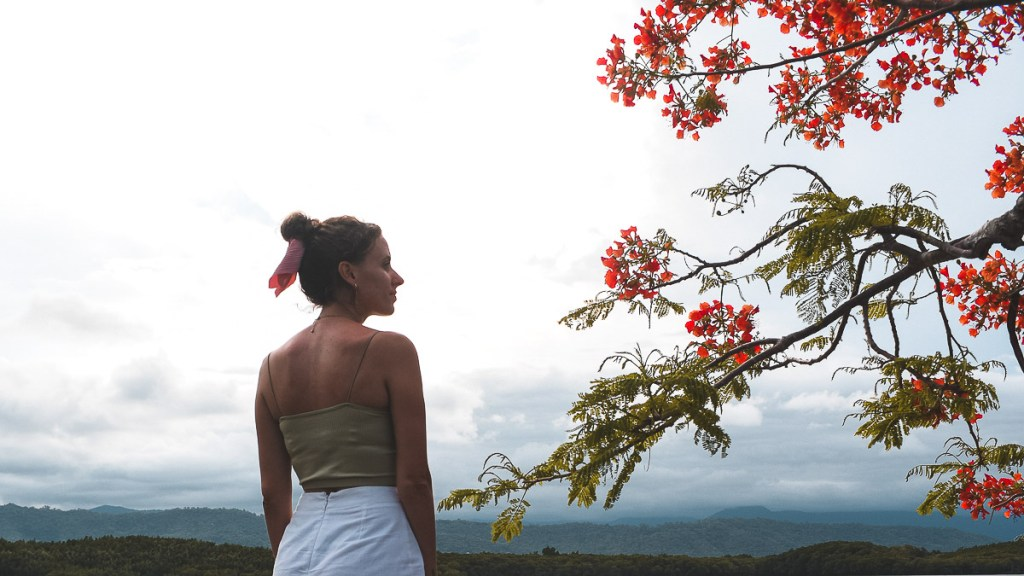 Girl next to red flowers at Port Douglas