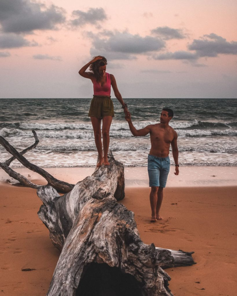 kerrie and woody holding hands on dead tree on Wongaling Beach at sunset