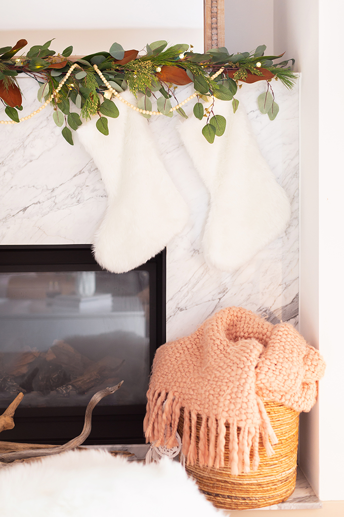 December 2018 Soundtrack + Bonus 2018 Soundtrack | Canadian Tire CANVAS Pre-lit Eucalyptus Leaves Garland with added greenery, magnolia leaves and wooden beads | Marble Fireplace with 2 faux fur stockings | Bohemian, Mid Century Modern Holiday Decor | Bohemian, Mid Century Modern Holiday Decor | Bohemian Holiday Home Tour 2018 // JustineCelina.com
