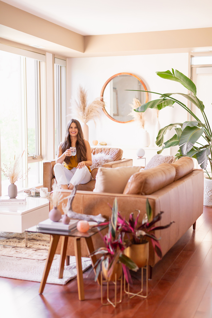 MidSummer Space Refresh Update | Smiling brunette woman enjoying a glass of white wine in her bright and airy mid century modern living room during the summer | Brunette woman wearing a knit tank top and white cropped jeans sitting on her coffee table | A Bohemian, Mid-Century Modern Living Room featuring Pampas Grass | Summer Decor 2019 Trends | Bohemian, Mid Century Modern Decor | Calgary Lifestyle, Interior Design and Home Decor Blogger // JustineCelina.com