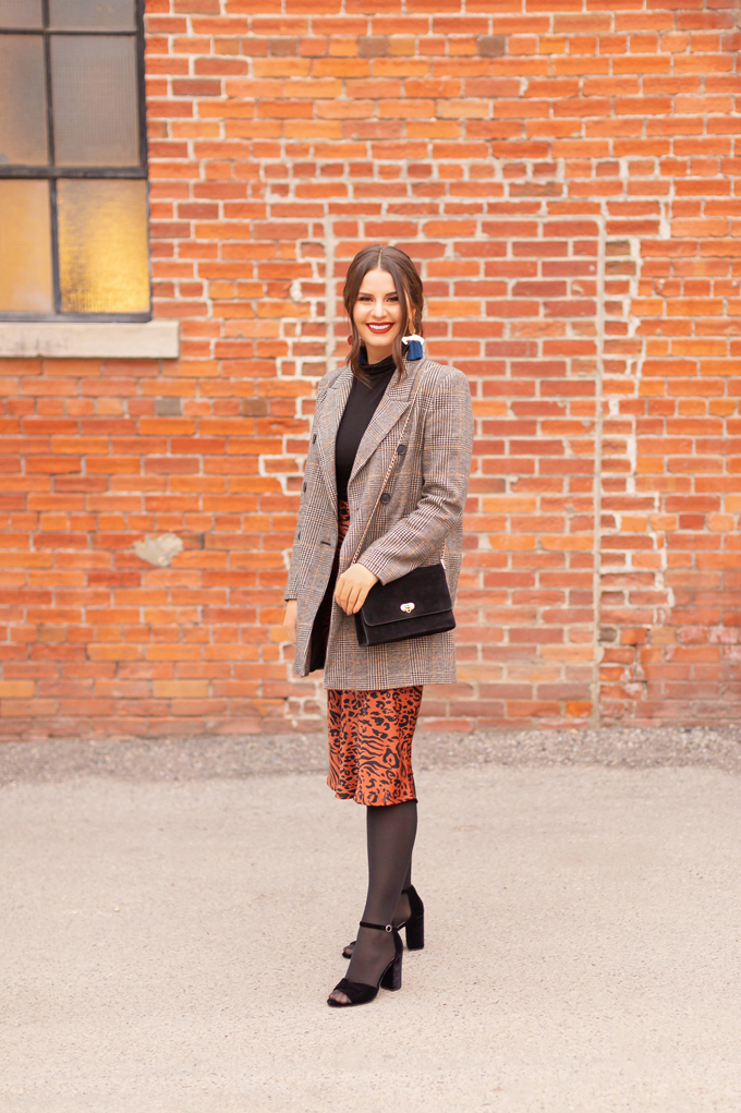 Autumn 2019 Lookbook: Cheetah Chic   Top Fall / Winter 2019 Trends   Top Autumn 2019 Trends and How to Wear Them   Brunette woman wearing a burnt orange cheetah print satin midi skirt, black turtleneck, oversized plaid blazer, black velvet sandals and a vintage suede bag   Chic Fall / Winter 2019 Evening Outfits   How to Style Cheetah Print   How to Style Boyfriend Blazers   How to Mix Prints   Top Calgary Fashion & Creative Lifestyle Blogger // JustineCelina.com