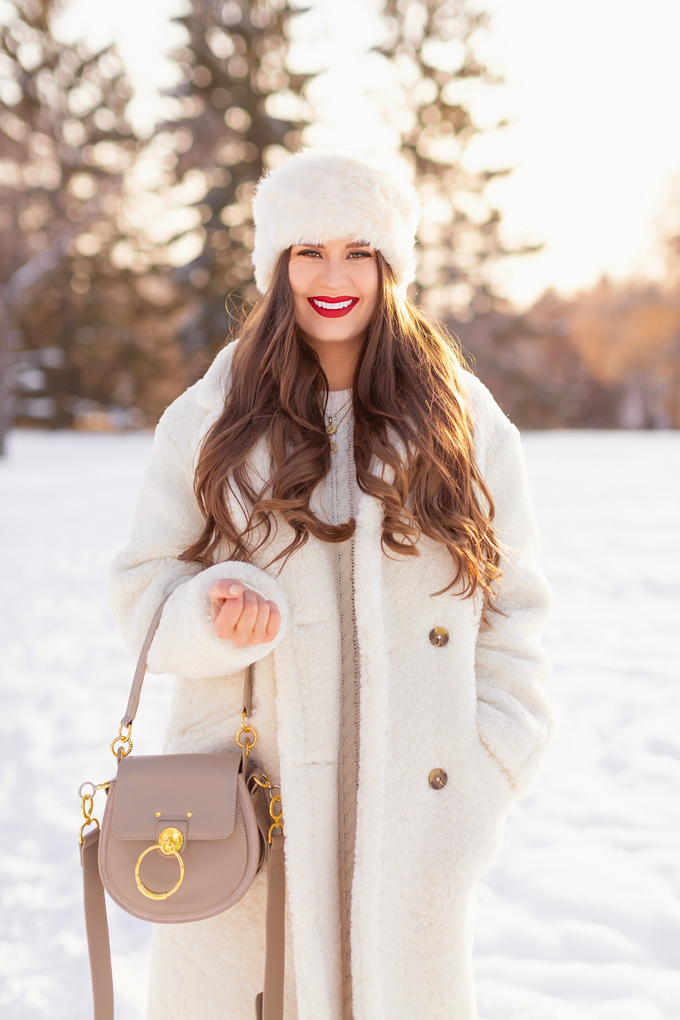 Autumn / Winter 2019 Lookbook: Winter Whites | Top Fall / Winter 2019 / 2020 Trends | Top Winter 2019 Trends and How to Wear Them | Brunette woman wearing a Mango Oversized Cream Teddy Coat, Cream Cable Knit Sweater Dress | Monochromatic Cream / White Outfit | Festive Winter Holiday Outfit | Christmas Dinner Outfit | Canadian Winter Outfit Ideas | How to Style a Faux Fur Headband | Fenty Stunna Lip Paint in Uncensored | Top Calgary Fashion & Beauty Blogger // JustineCelina.com