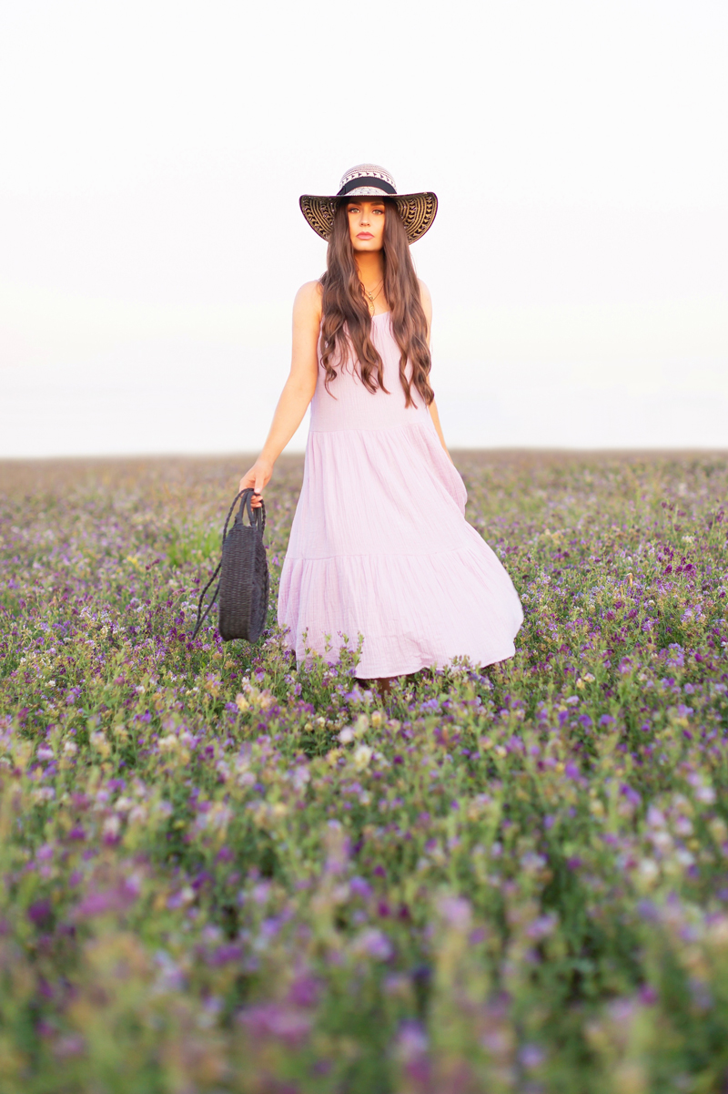 Summer 2020 Lookbook | Boho Summer 2020 Outfit Ideas | Summer Capsule Wardrobe | Summer Quarantine Outfits | Classic Summer Outfit Ideas | The Best Cotton Dresses 2020 | Sunset Photoshoot | Summer to Fall Outfit Ideas | Classic Affordable Summer Style | Summer 2020 Trends | Brunette woman wearing a lilac H&M Crinkled Cotton Dress, Oversized Black Patterned Straw Hat and Black Circular Straw Bag in a field of purple alfalfa at sunset | Calgary Alberta Fashion Blogger // JustineCelina.com