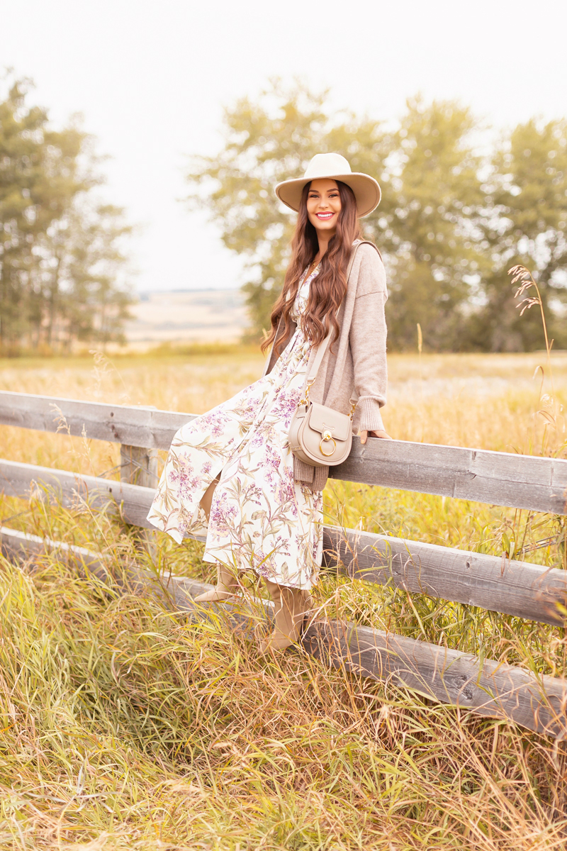 Early Autumn 2020 Lookbook | Country Checks | Smiling brunette woman wearing a botanical print button down midi dress, a Chloe Tess Bag in Grey, knee high suede pointed toe boots and a taupe flat brimmed hat next to an weathered fence in the prairies | Boho Fall 2020 Outfit Ideas | Top Fall 2020 Trends | How to Style Midi Dresses for Fall | Bohemian Fall outfit Ideas | How to Wear Florals in Fall | Cottagecore Fall Outfit Ideas | Calgary Alberta Fashion & Lifestyle Blogger // JustineCelina.com