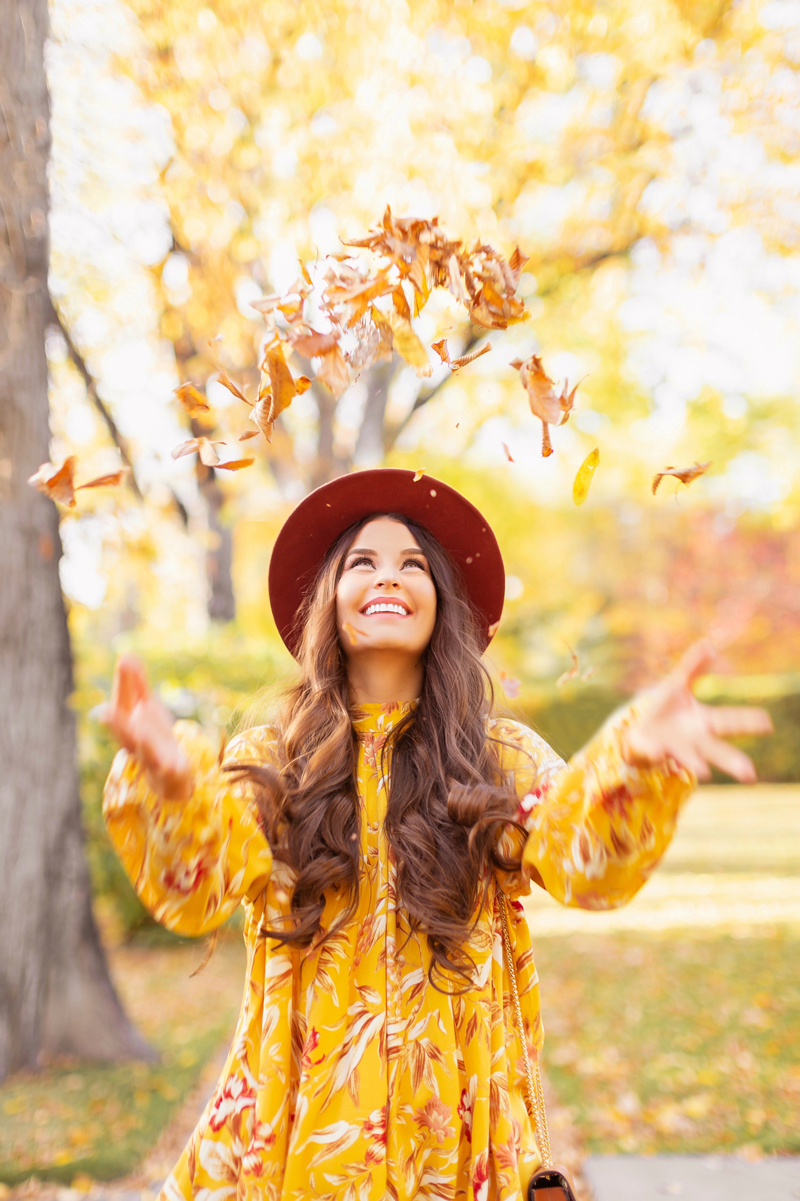 Early Autumn 2020 Lookbook |  Laughing brunette woman wearing a rust fedora and a mustard yellow botanical print shift dress throwing leaves into the air on a sunny autumn afternoon | warm weather fall outfit ideas | Fall 2020 Trend Guide | Casual Fall Fashion | Boho Fall 2020 Outfit Ideas | Fall in Calgary | Thanksgiving Outfit Ideas | | Transitional Summer Meets Autumn Fashion | October Style | Fall Fall Photoshoot | Calgary Alberta Fashion & Lifestyle Blogger // JustineCelina.com