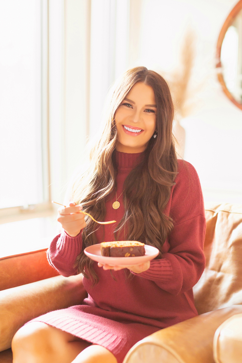 Gluten Free Mapled Pumpkin Chai Bread   Smiling brunette woman wearing a pink sweater dress enjoying a slice of healthy pumpkin bread in her bright and airy living room   Easy Pumpkin Bread   Moist Pumpkin Bread   The Best Gluten Free Fall Baking Recipes   No Sugar Pumpkin Bread   Maple Syrup Pumpkin Bread   Pumpkin Bread Cake   Healthy Pumpkin Bread   Free From Pumpkin Bread   Calgary Plant Based Food Blogger // JustineCelina.com