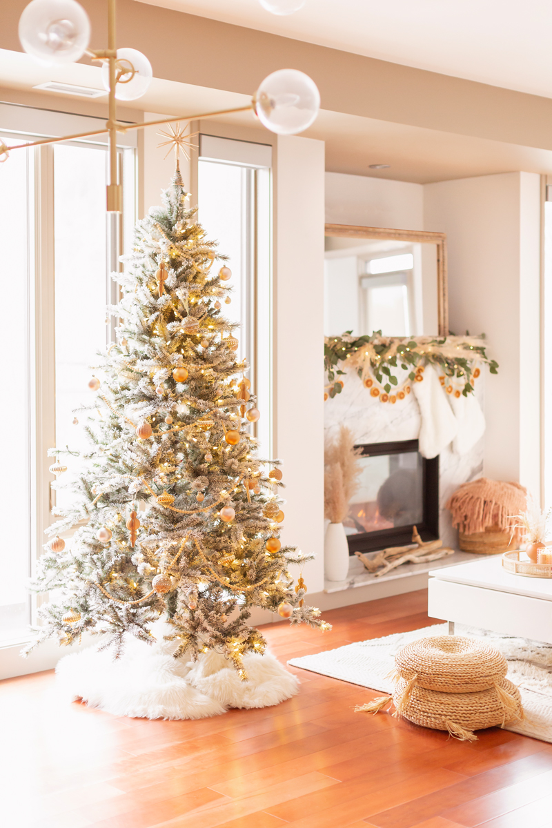 Mid Century Meets Boho Holiday Decor | Bright and airy Mid Century Modern Living Room with a Flocked Christmas Tree and Sputnik Metallic Tree Topper | Mid Century Modern Christmas Tree Skirt | Boho Christmas Decorating Ideas for Apartments | Flocked Christmas Tree with Wood Garland, Metallic and Wood Ornaments | Bohemian Holiday Home Tour 2020 | Boho Chic Christmas Decor | Glam neutral holiday decor | Pampas Grass Holiday Arrangement | Boho Christmas Tree // JustineCelina.com