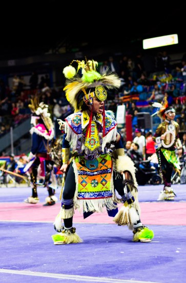 A pow wow dancer with an intense look in mid-dance.