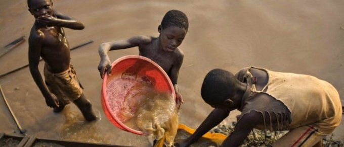 Boys pan for gold at a riverside at Iga Barriere in the resource-rich Ituri region of eastern Congo