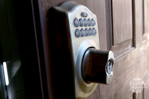 The Schlage Keypad Deadbolt against the peeling paint and partially stripped fiberglass door.