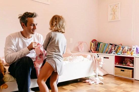 """Pai vestindo sua filha - Imagem de Mika Amanto, do projeto """"A day in the life of..."""", que mostra cotidianos de famílias pelo mundo."""