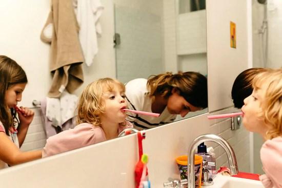 """Crianças escovando os dentes - Imagem de Mika Amanto, do projeto """"A day in the life of..."""", que mostra cotidianos de famílias pelo mundo."""