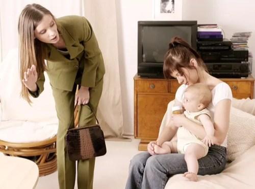 Mãe de terninho sai para o trabalho e acena para filho, sentado no colo da babá