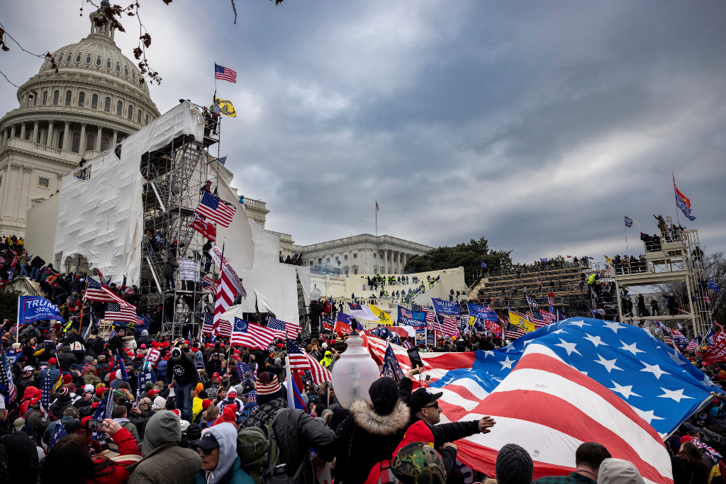 Trump supporters storm the U.S. Capitol on January 6, 2021. They cover the stairs and the bleachers set up for the inauguration. They carry American flags, Trump flags, anti-Semitic flags, and other white supremacist flags.