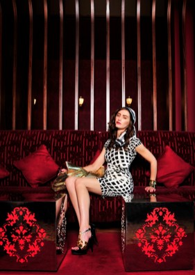 Female model sitting on red couch.