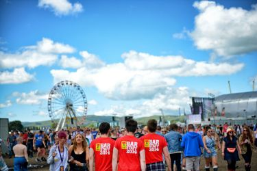 3 male bar staff walking through T in the Park.