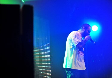 Rapper on stage with microphone in hand backlit with a blue light.