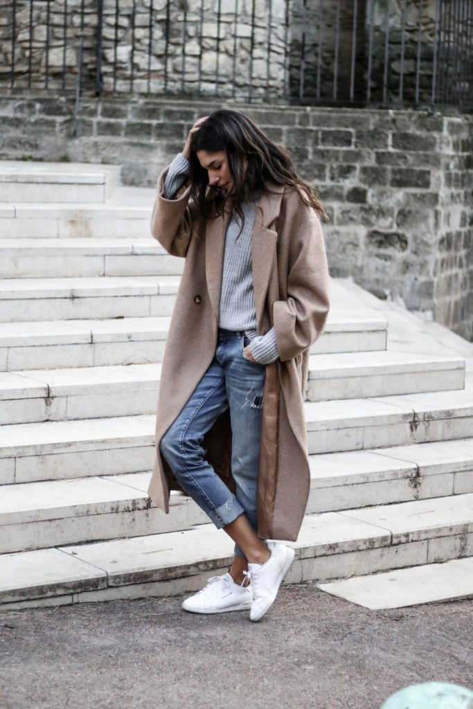 An effortless city style, this over-sized taupe trench complements distressed boyfriend style jeans and white sneakers. Casual tousled hair makes this look low-key and approachable. Via Federica L. Coat: H&M, Sweater & Shoes: Missguided, Jeans: Zara, Rings: Lily's Creations, Cross Model, Be Maad, Thomas Sabo, Earrings: Lily's Creations