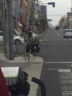 Japan rondfietsen met te veel bagage en een groot bord achterop.