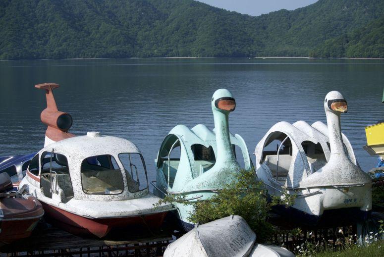 Voor de afdaling fietsen we eerst nog een stuk rond het meer, dat bevolkt wordt door aftandse bootjes in de vorm van zwanen, helicopters, auto's en meer.
