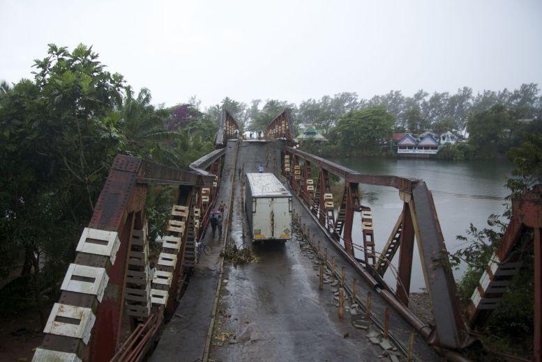 Middenop de ingestorte brug staat de boosdoener nog. Brug en vrachtwagen zijn ondertussen een soort toeristische attractie.