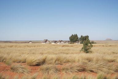 Rode aarde, geel gras, blauwe lucht, witte huisjes, en zowaar wat groene bomen.