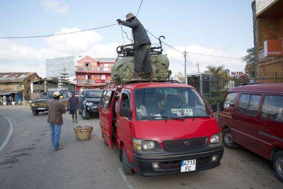 Fietsen worden bovenop de taxi brousse vakkundig vastgeknoopt.