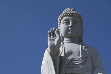 Het 7 meter grote Boeddha beeld komt mooi uit tegen de ondertussen weer blauwe lucht.