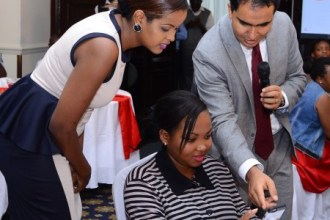 Airtel Kenya CEO Adil El Youssefi takes Viola Kipchumba (center) through the process of subscribing to Airtel UnlimiNET. Looking on is radio personality Amina Abdi.