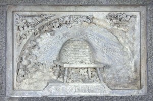 "A rectangular stone plaque dominated by a central relief carving of a beehive with the words ""Holiness to the Lord"" above and the word ""Deseret"" below."