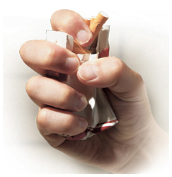 A person crushing a pack of cigarettes