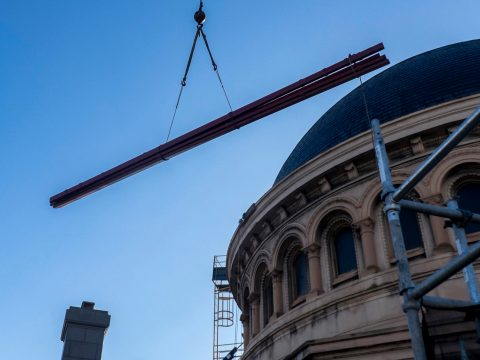 the shot looks up a the dome of the synagogue as a crane lifts a piece of rebar overhead