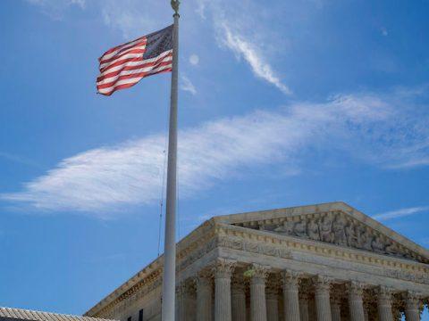 the supreme court under a blue sky, flag waving