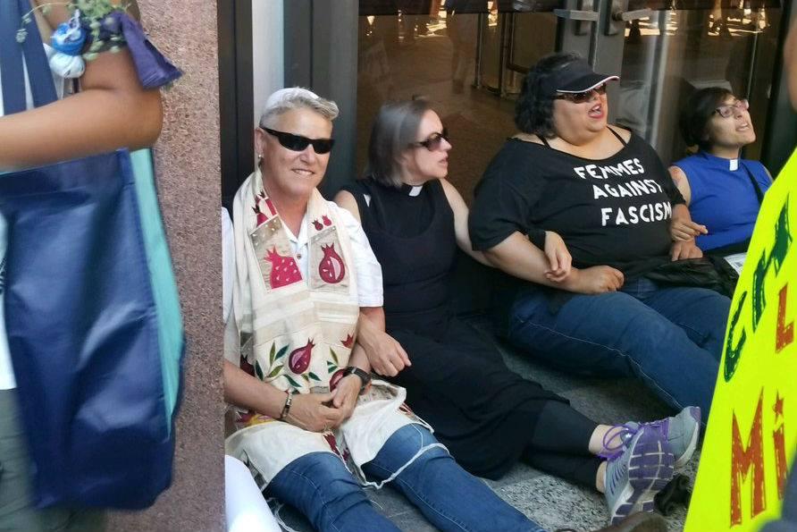 Sue Reinhold of Berkeley (left, wearing tallit and sunglasses) blocks the