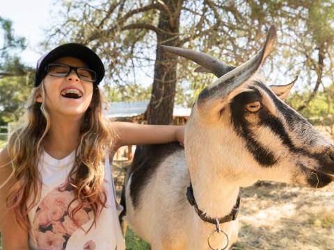 A happy camper with a goat at Eden Village West summer camp. (Photo/Courtesy Eden Village West)