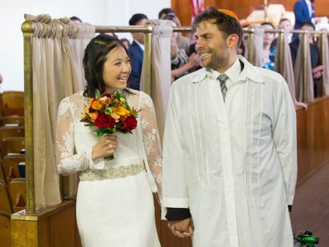 Vy Nguyen and Andrew Koller walk down the aisle at their wedding at Congregation Chevra Thilim in San Francisco.