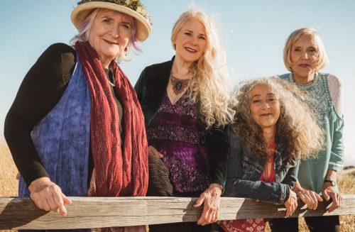 four older women smiling, leaning on a wooden fence on a hillside