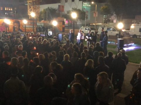 a large crowd standing together at night
