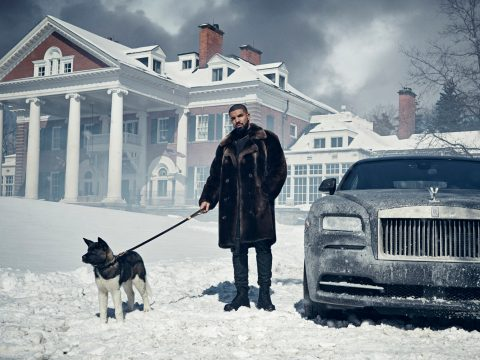 Drake stands in the snow, holding a dog by the leash, with a mansion in the background, next to Rolls Royce