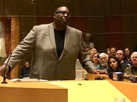 a black man stands at a podium giving a speech