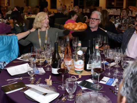 Guests at the table of winemaker John Bonick of Art House Wines say the hamotzi. (Photo/Janna Waldinger, Art & Clarity Photography)