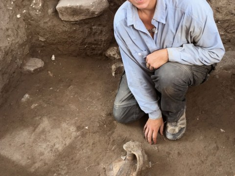 a young woman kneels next to partially unearthed pottery artifacts