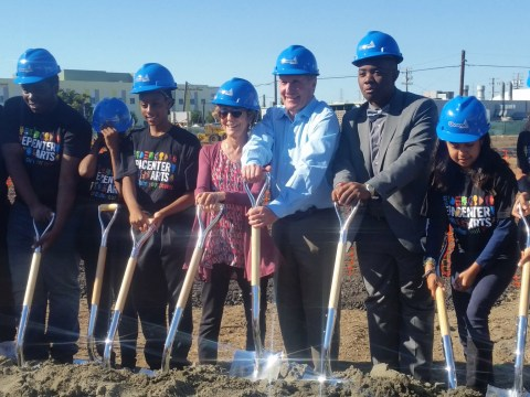 a row of people, teens of color and the goldmans, all in blue hardhats with golden shovels