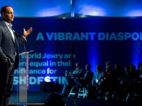 """a man stands speaking at a podium. a banner in the background reads """"A VIBRANT DIASPORA"""""""